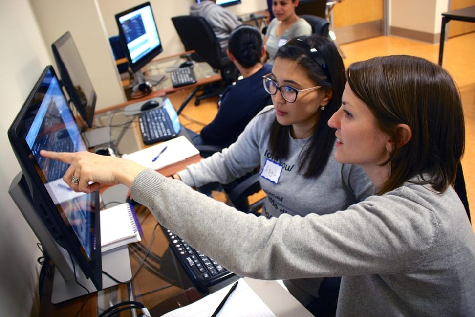 Two women sit at a computer, working together on some code.